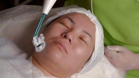 Darsonvalization Close-up van het gezicht van een Moslimvrouw op de procedure van de fysiotherapie gezichtsverjonging Activering  stock footage