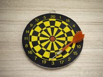 Dart arrow and dartboard on brown wooden background royalty free stock image