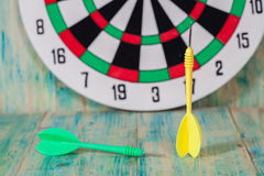 Dart arrow and dartboard. On table royalty free stock image