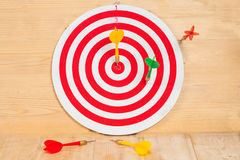 Dart arrow and dartboard on wood Royalty Free Stock Photo