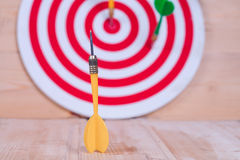 Dart arrow and dartboard on wood Royalty Free Stock Image