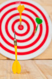 Dart arrow and dartboard on wood. Background Royalty Free Stock Photography