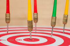 Dart arrow and dartboard on wood. Background Stock Images