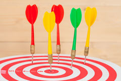 Dart arrow and dartboard on wood. Background Royalty Free Stock Image