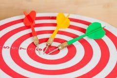 Dart arrow and dartboard on wood. Background Stock Image