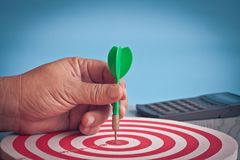 Dart arrow in hand on target dartboard ,Business success concept stock photo