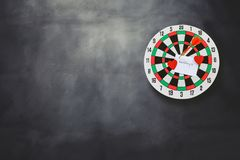 Dart arrow hitting in bullseye on dartboard with black royalty free stock photo