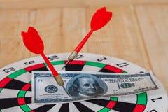 Dart arrow hitting in bullseye on dartboard Stock Images