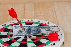 Dart arrow hitting in bullseye on dartboard Stock Photo