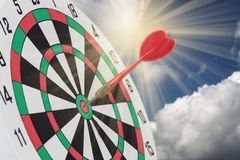 Dart arrow hitting in bullseye on dartboard with sky royalty free stock photos