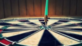 Dart arrow hitting red central target Stock Photography