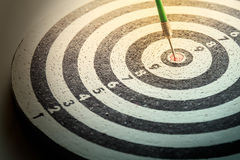 Dart arrow hitting in the target center of dartboard Royalty Free Stock Images