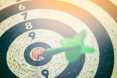 Dart arrow hitting in the target center of dartboard Royalty Free Stock Image