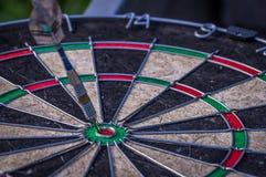 Dart arrow hitting in the target center of dartboard Stock Photos