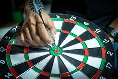 Dart arrow hitting in the target center of dartboard using as background Target business, achieve and victory,success concept.  Royalty Free Stock Photography