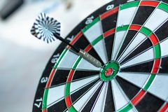 Dart arrow hitting in the target center of dartboard using as background Target business, achieve and victory,success concept.  Royalty Free Stock Image