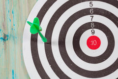 Dart arrow missed in the target of dartboard. Dart arrow missed in the target center of dartboard royalty free stock photo