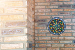 Dart arrow missing the center of target. dartboard on brick wall Royalty Free Stock Photos