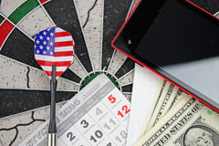 Dart arrow, phone, dollars and pad Stock Photos
