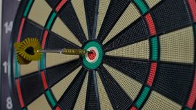 A dart arrow stick on the center of dart board bull eye stock video