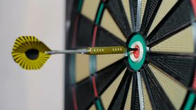 A dart arrow stick on the center of dart board bull eye stock footage