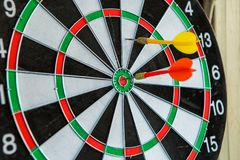 Dart arrows hitting in the target center of dartboard Royalty Free Stock Image