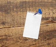 Dart in blank notepad. On a vintage wooden board Royalty Free Stock Photo