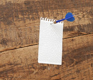 Dart in blank notepad. On a vintage wooden board Royalty Free Stock Photos