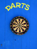 Dart board. Mounted on wooden wall with darts painted above stock photo