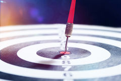 Dart board with arrow, business target symbol. Arrow in center of dart board, symbol image for success or goal achievement in business; colorful bokeh and lens Stock Image