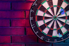 Dart board on a brick wall with dramatic lighting Royalty Free Stock Photography
