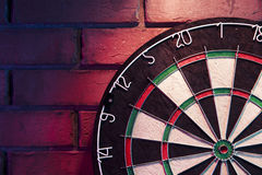 Dart board on a brick wall with dramatic lighting Stock Photos