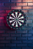 Dart board on a brick wall with dramatic lighting Stock Image