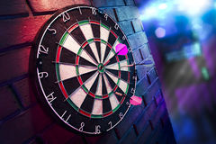 Dart board on a brick wall with dramatic lighting stock images
