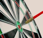 Dart board with color arrow hitting target, closeup. Dart board with color arrow hitting target on light background, closeup stock photos
