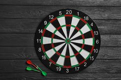 Dart board with color arrows on black wooden background. Top view royalty free stock photography