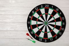Dart board with color arrows on white wooden background. Space for text. Dart board with color arrows on white wooden background, top view. Space for text royalty free stock image