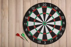 Dart board with color arrows on wooden background. Space for text. Dart board with color arrows on wooden background, top view. Space for text stock photo