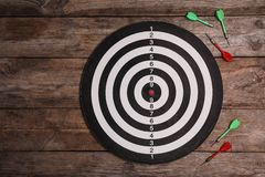 Dart board with color arrows on wooden background. Space for text. Dart board with color arrows on wooden background, top view. Space for text stock image
