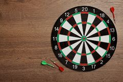 Dart board with color arrows on wooden background. Space for text. Dart board with color arrows on wooden background, top view. Space for text royalty free stock photos