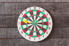 Dart board with darts arrow in the target center on wood backgro. Und Stock Photos