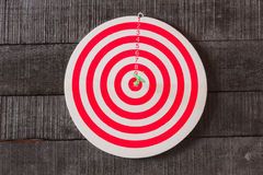 Dart board with darts arrow in the target center on wood backgro. Und Stock Image
