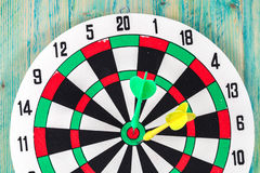 Dart board with darts on background Royalty Free Stock Photo