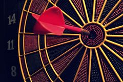 Dart Board On Target. Dart board that has a dart in the center target, with selective focus Stock Image