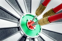 Dart board with red arrows hitting target. Closeup royalty free stock photography