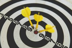 Dart on board right direction hit target goal. Competition game to win focus on achievement with smart thinking planning accurate. Three yellow dart on board stock photo