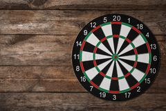 Dart board on wooden background. Space for text. Dart board on wooden background, top view. Space for text royalty free stock images