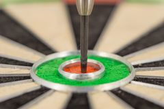 Dart in bull& x27;s eye, close up. Dart in bull& x27;s eye, close up green and red Royalty Free Stock Image