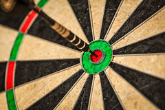 Dart in bull's eye close up Royalty Free Stock Photo