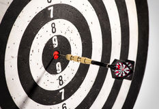 Dart in the bulls eye center of a dart board Stock Images